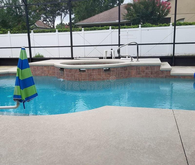 Zwembad in het schermbijlage met pooldek en kuuroordjacuzzi stock foto's