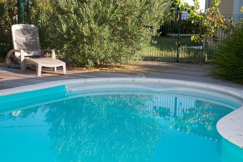Zwembad met blauw transparant water op een tuingebied royalty-vrije stock afbeelding