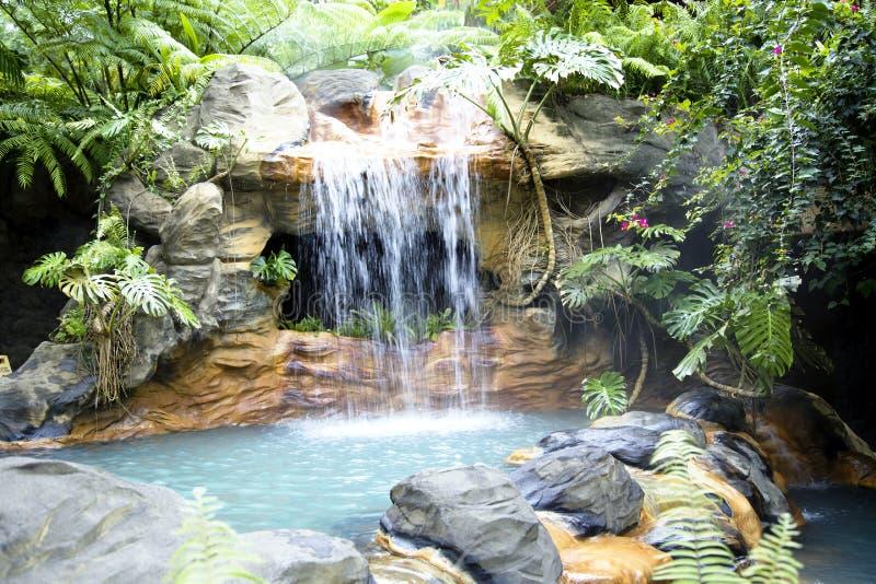 Zwembad met een waterval en een heet thermisch water stock foto's