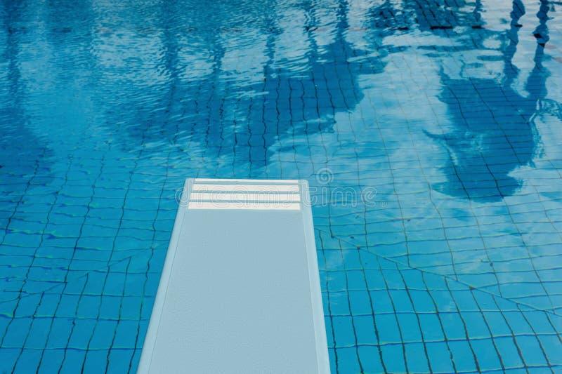 Zwembad met het verfrissen van blauwe water, springplank en bezinning royalty-vrije stock foto's