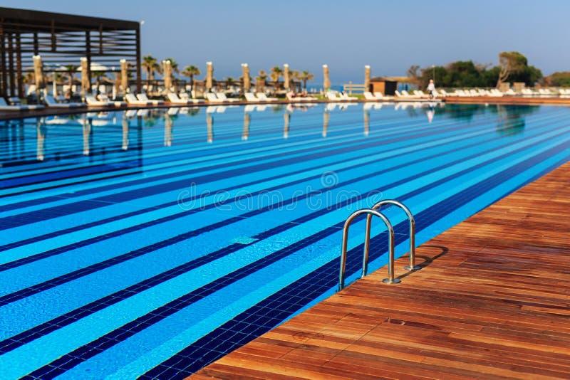 zwembad met houten banken 's morgens met palmbomen op strandparaplu ' s gestapelde zon royalty-vrije stock afbeelding