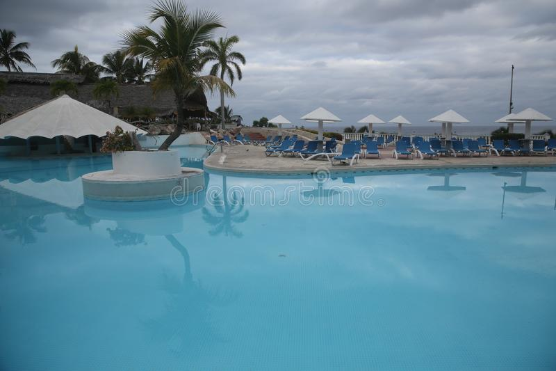 Zwembad met palmen en de lanterfanter en paraplu met ruimte voor tekst royalty-vrije stock afbeeldingen