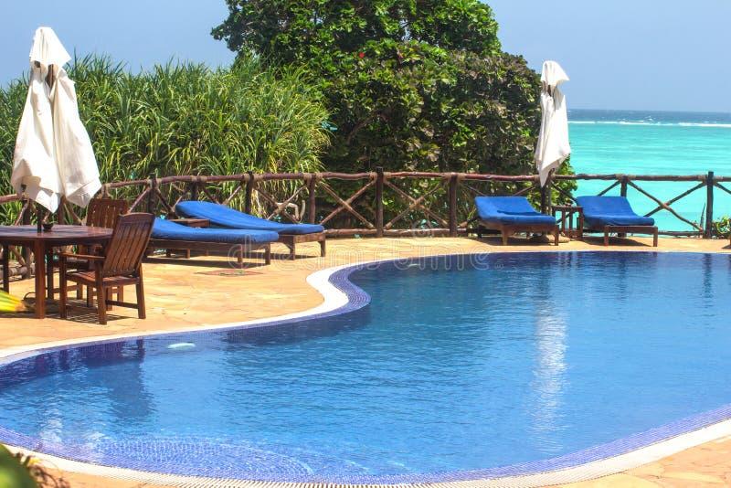 Zwembad met sunbeds en paraplu's royalty-vrije stock afbeeldingen