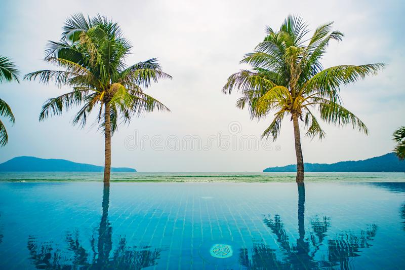 Zwembad op de achtergrond van het overzees op het eiland Het vlotte water van pool wijst op hoge schilderachtige palmen in een st stock afbeelding