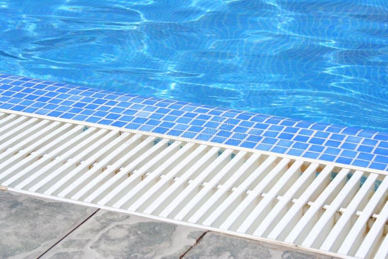 Zwembad wit grating traliewerk met duidelijk blauw water en grijze tegels stock afbeeldingen
