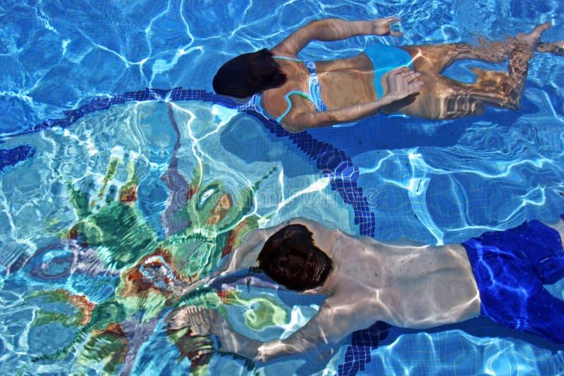 Zwemmen van het paar onderwater in duidelijke blauwe pool stock foto's