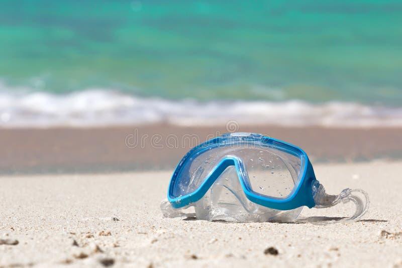 Zwemmend masker op wit zand stock foto's