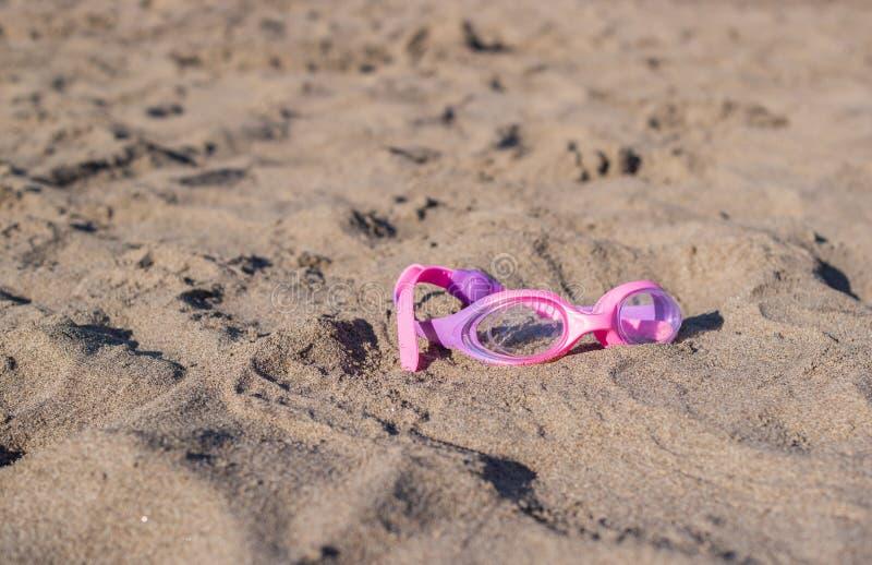 Zwemmende beschermende brillen op zand stock foto