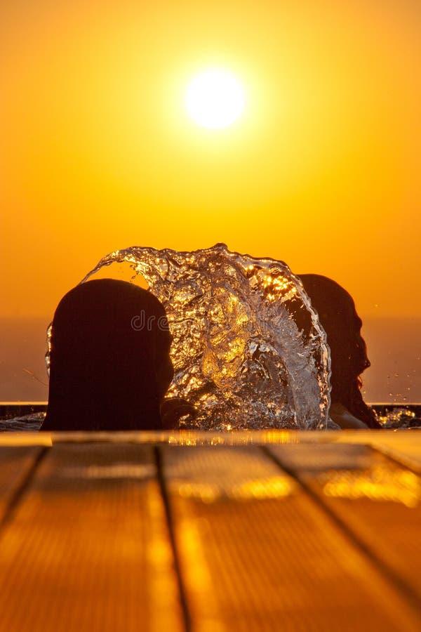 Zwemmende meisjessilhouetten en bespattend water tegen overzees bij su stock afbeelding