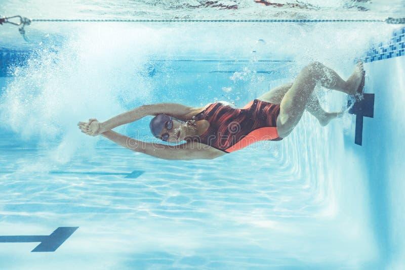 Zwemmer in actie binnen zwembad stock foto