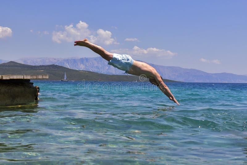 Zwemmer die aan zeewater springen stock foto