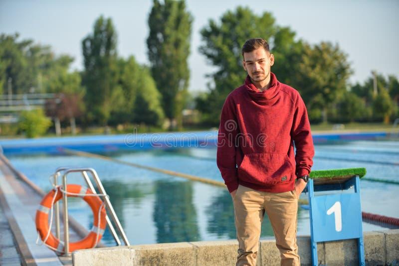 Zwemmer die zich naast een pool op een zonnige ochtend bevinden stock fotografie