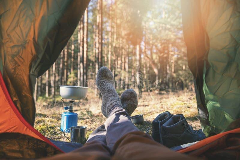 Zwerflust het openlucht kamperen - reizigersvoeten uit de tent royalty-vrije stock fotografie