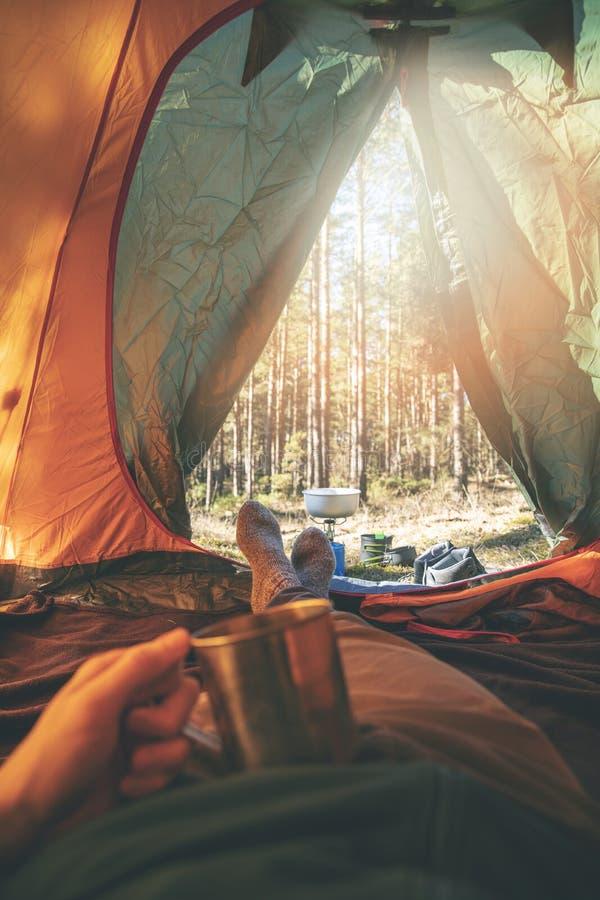 Zwerflust - mens het ontspannen in tent na stijging met kop thee stock foto