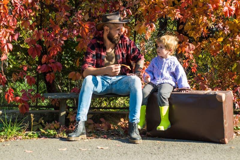 Zwerflustconcept Avontuur met zoon Het vertellen verhalen over afgelopen tijden Vader met koffer en zijn zoon Gebaarde papa stock fotografie