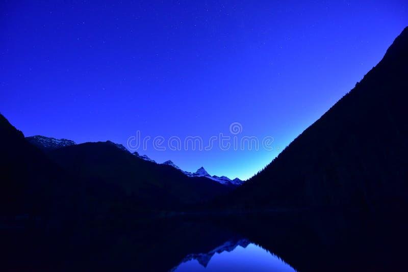 Zwerver die door bergen wordt omringd stock afbeelding