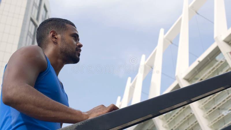 Zwetende mannelijke atleet die zich op trappen bevinden, die voor geschikt lichaam, het actieve leven aanstoten stock afbeeldingen