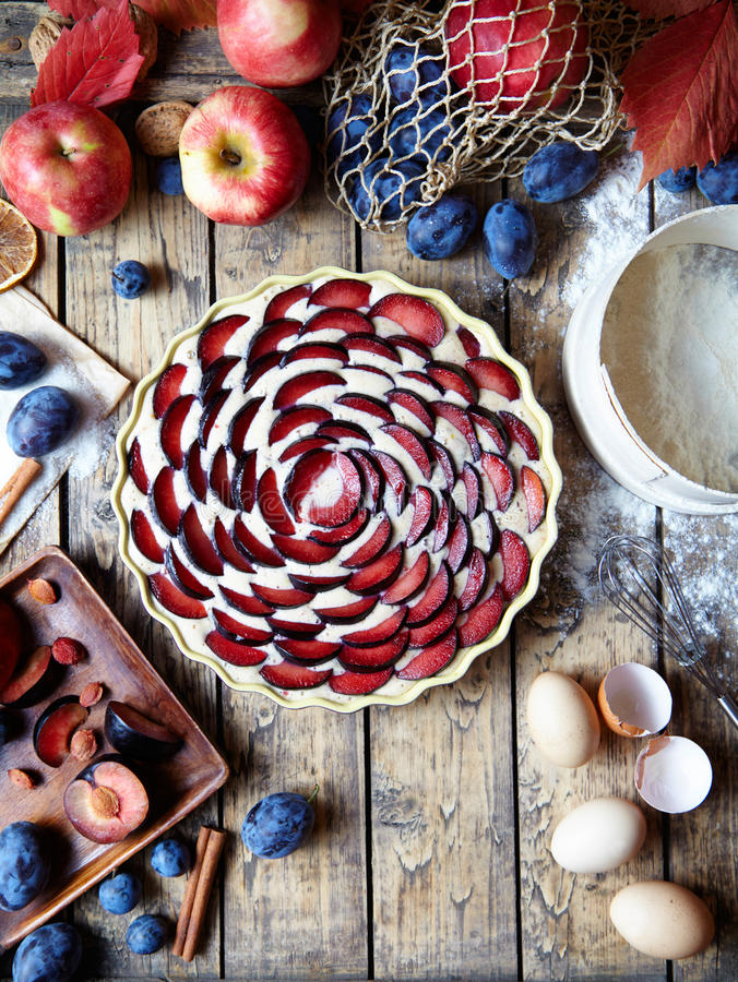 Zwetschgendatschi hecho en casa de la torta del ciruelo de la preparación Ingredientes Estilo rústico Visión superior fotografía de archivo