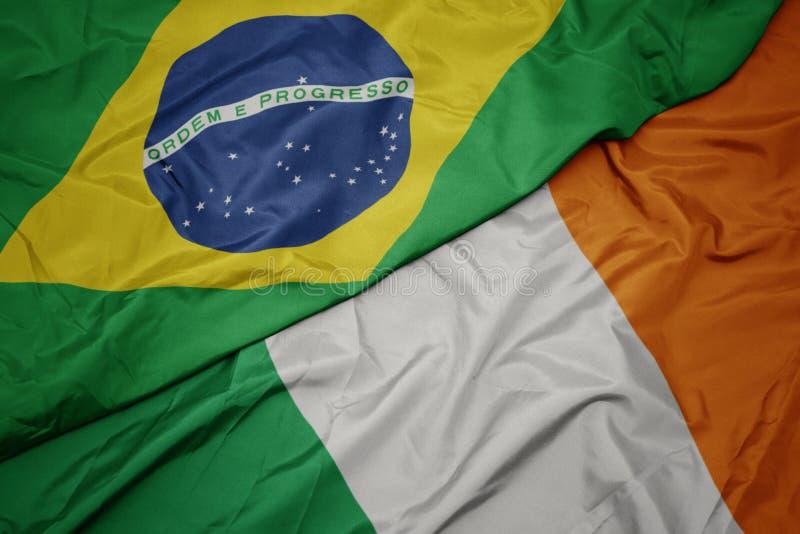 zwevende , kleurrijke vlag van ierland en nationale vlag van brazilië royalty-vrije stock afbeeldingen