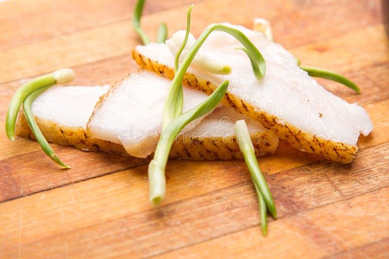 Zwiebel und Fett auf der hölzernen Platte stockbild