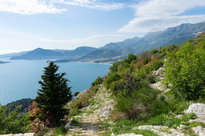 Zwiedzać Adriatic wybrzeże w Budva, Montenegro faleza z zieloną górą, błękitne wyspy i morze i Ślad chodzić plaża obrazy stock