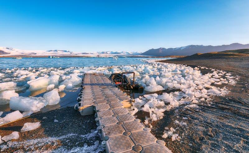 Zwiedzający łódkowaty wiązany puszek blisko brzeg Jokulsarlon lodowa laguna przy zmierzchem fotografia royalty free