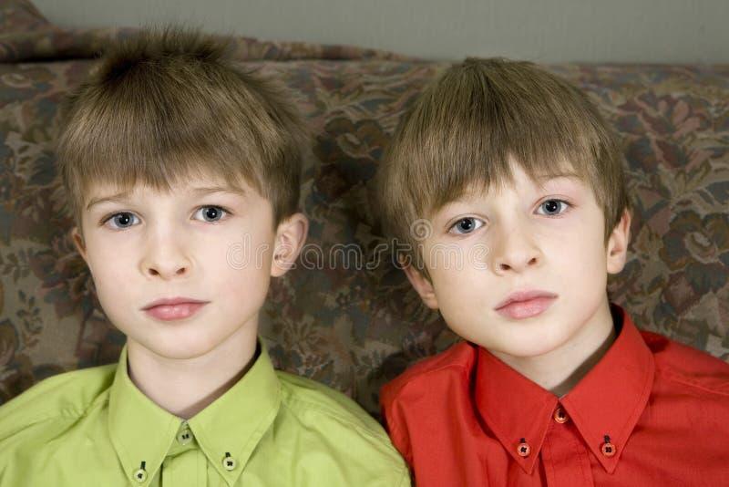 Zwillingbrüder, die zusammen sitzen stockfotografie