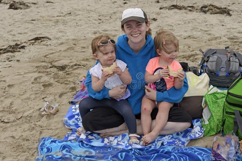 Zwillinge, die das Mittagessen auf dem Strand mit Mutter essen lizenzfreie stockfotografie