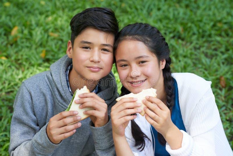 Zwillinge, die Sandwiche essen stockbild