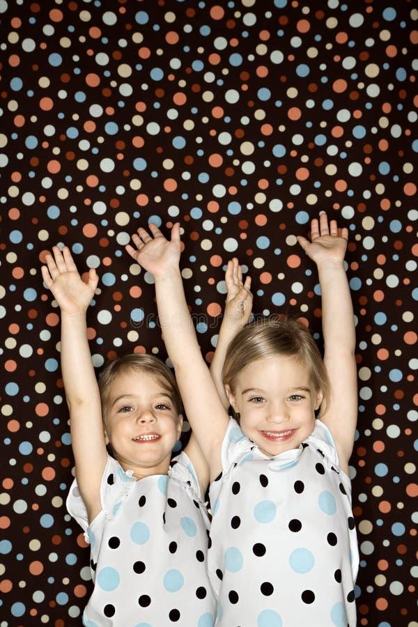 Zwillinge mit den Armen angehoben. lizenzfreie stockbilder