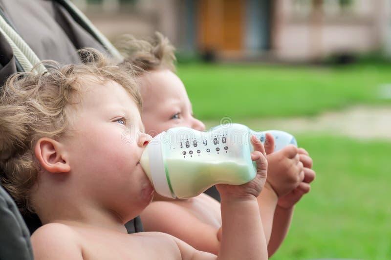 Zwillinge saugen eine Flasche mit Milch stockbild