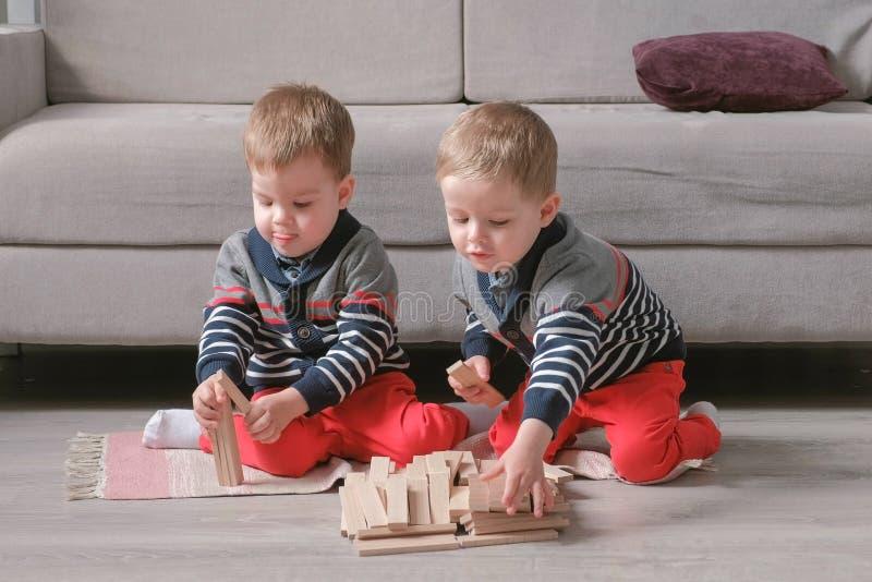 Zwillingsjungenbrüder sind von den Holzklötzen im Bau, die auf dem Boden durch das Sofa in ihrem Raum sitzen lizenzfreie stockfotografie