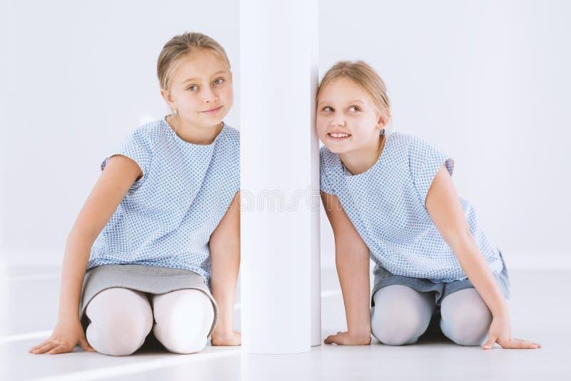Zwillingsschwestern auf Gegenseiten stockfotos