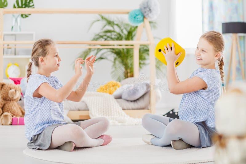 Zwillingsschwestern, die im Klassenzimmer spielen lizenzfreie stockfotografie