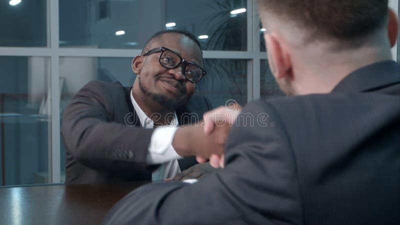Zwischen verschiedenen Rassen Geschäftsmänner, die Hände in der Geschäftshalle, lächelnd rütteln stockfotografie
