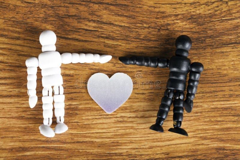 Zwischen verschiedenen Rassen Liebeskonzept mit hölzernen Figürchen auf hölzernem Hintergrund lizenzfreie stockfotos