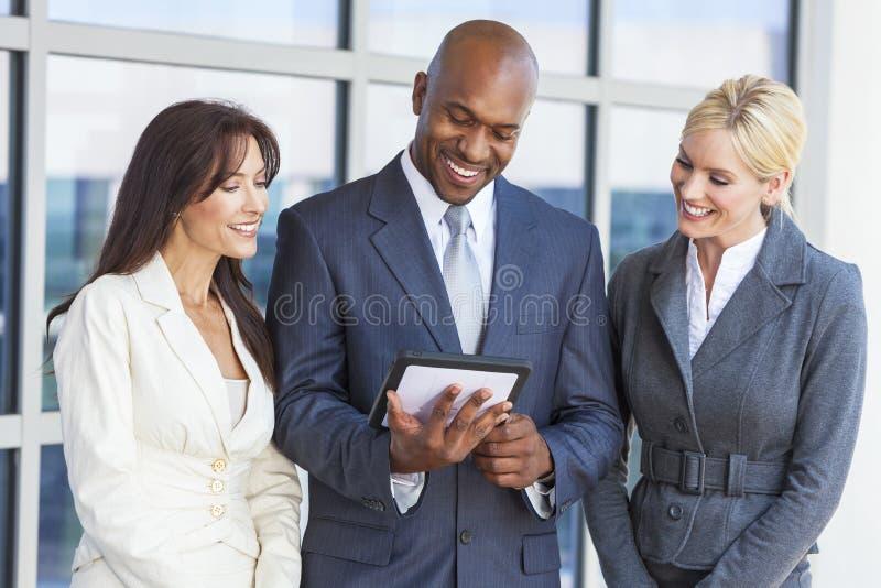 Zwischen verschiedenen Rassen Mann-u. Frauen-Geschäft Team With Tablet Computer stockbild