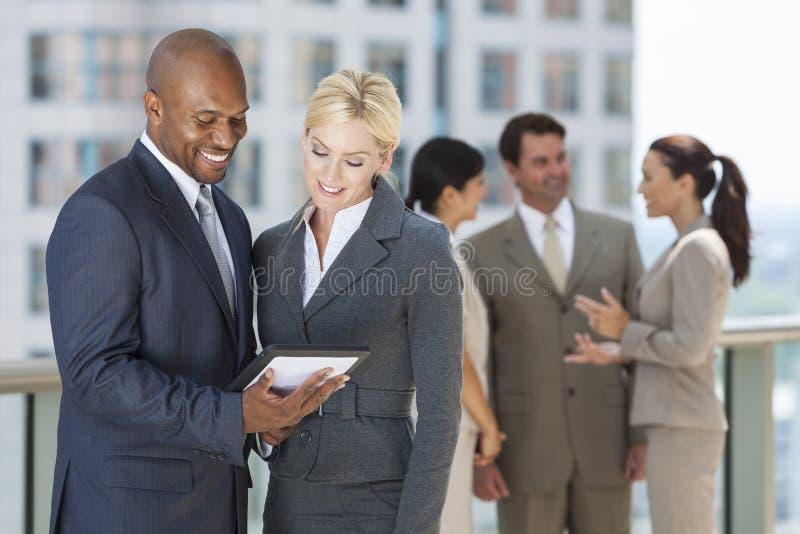 Zwischen verschiedenen Rassen Mann-u. Frauen-Geschäft Team With Tablet Computer stockbilder