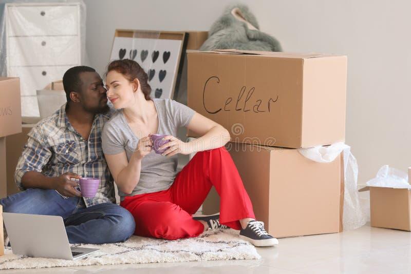 Zwischen verschiedenen Rassen Paare, die auf Boden mit Kästen und Schalen des Getränkes sitzen Bewegen in neues Haus stockbild