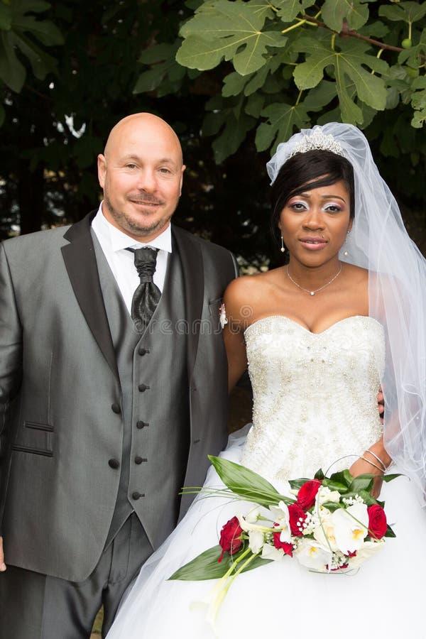 Zwischen verschiedenen Rassen Paarporträt-Afroamerikanerkaukasier, der Hochzeit nimmt stockfoto