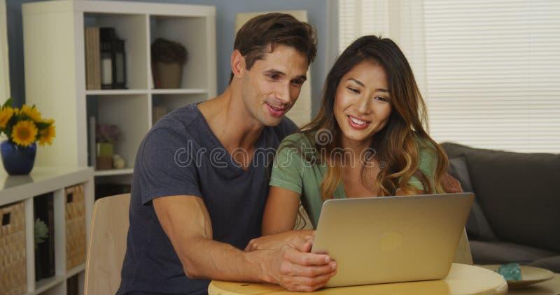 Zwischen verschiedenen Rassen Paarvideo, das mit Familie auf Laptop plaudert lizenzfreie stockbilder