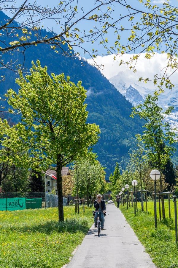 Zwitserland, die van de zon genieten die een fiets en een overweldigende mening berijden stock fotografie