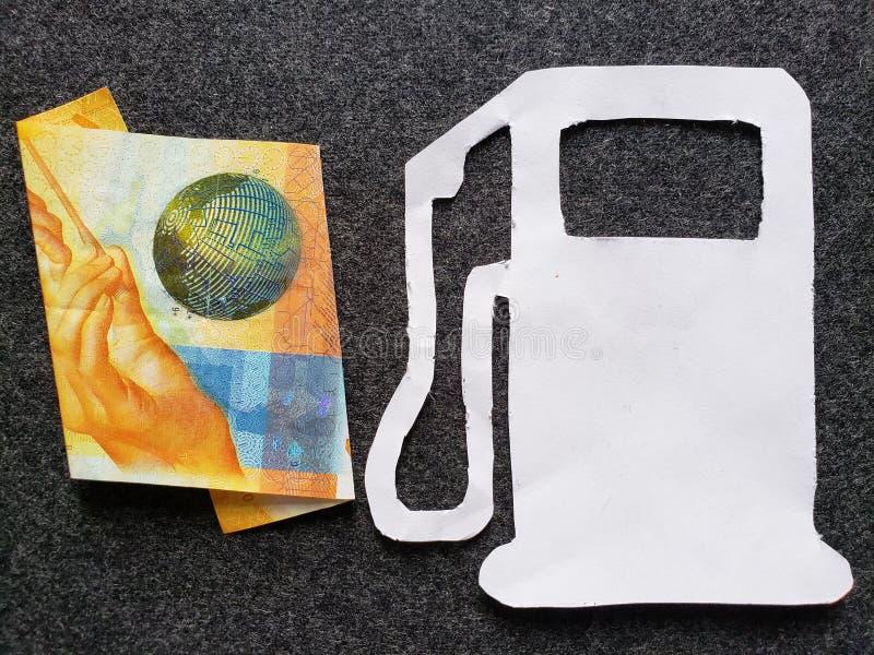 Zwitsers bankbiljet van tien franken en cijfer van benzinepomp in wit royalty-vrije stock foto