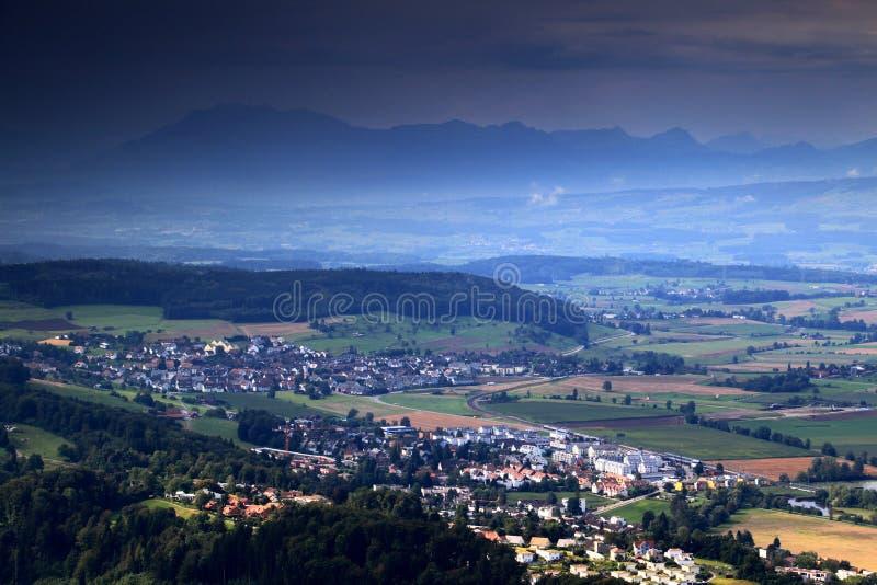 Zwitserse coutryside met dorpen, landbouwgrond, bos en bergen stock fotografie