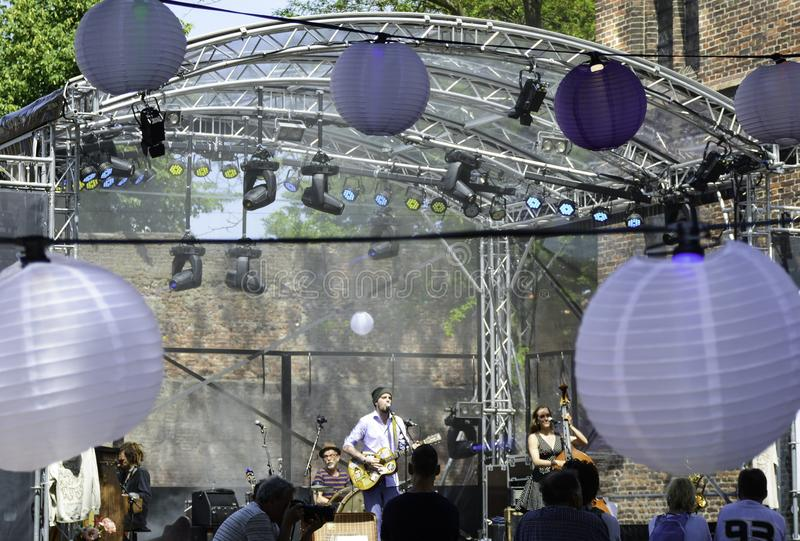 people listening to an outdoor concert. Performance of a music band on a stage with lights outdoor. Outdoor stock photo