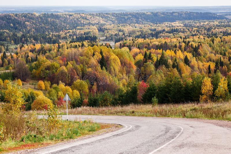 Zwrot droga, opuszcza w jesień Rosyjskim lesie z kolorowymi koloru żółtego, czerwieni i zieleni drzewami słoneczny dzień, obraz stock