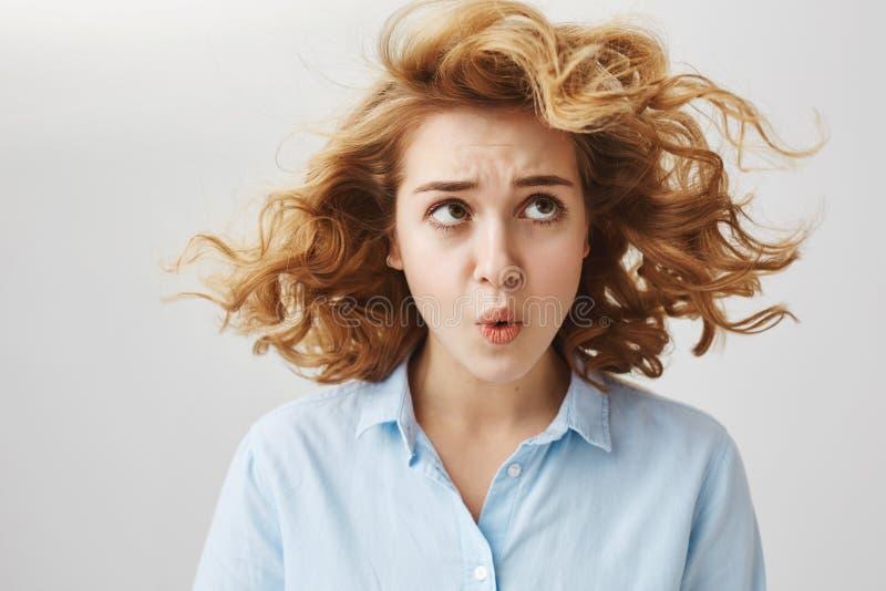 Zwrot ten wiatr Portret zmieszana i przeszkadzająca młoda kobieta z krótkim kędzierzawym włosy przyglądającym up na spławowym pas fotografia royalty free