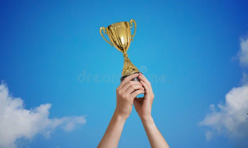 Zwycięzca trzyma trofeum w rękach przeciw niebieskiemu niebu obraz royalty free
