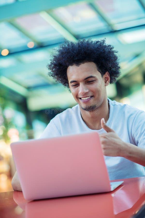 Zwyci?ski przystojny m??czyzna patrzeje jego laptop podczas gdy siedz?cy w jaskrawym ?ywym pokoju zdjęcia royalty free