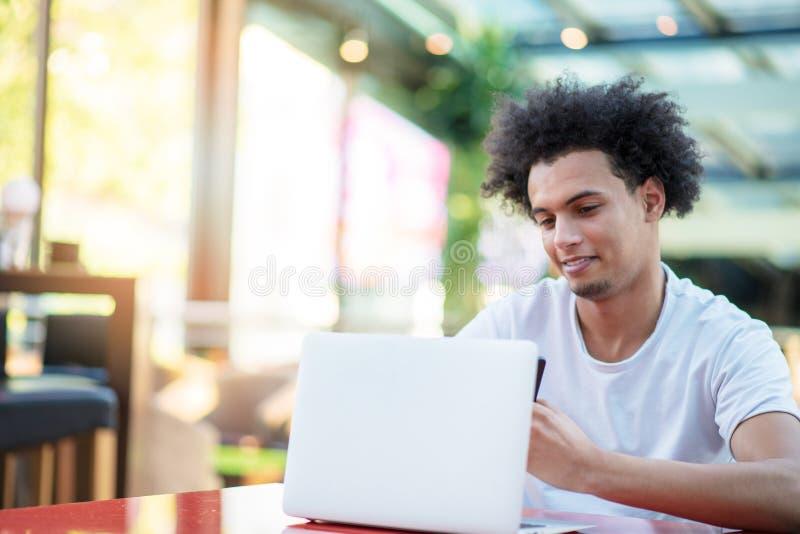 Zwyci?ski przystojny m??czyzna patrzeje jego laptop podczas gdy siedz?cy w jaskrawym ?ywym pokoju zdjęcia stock